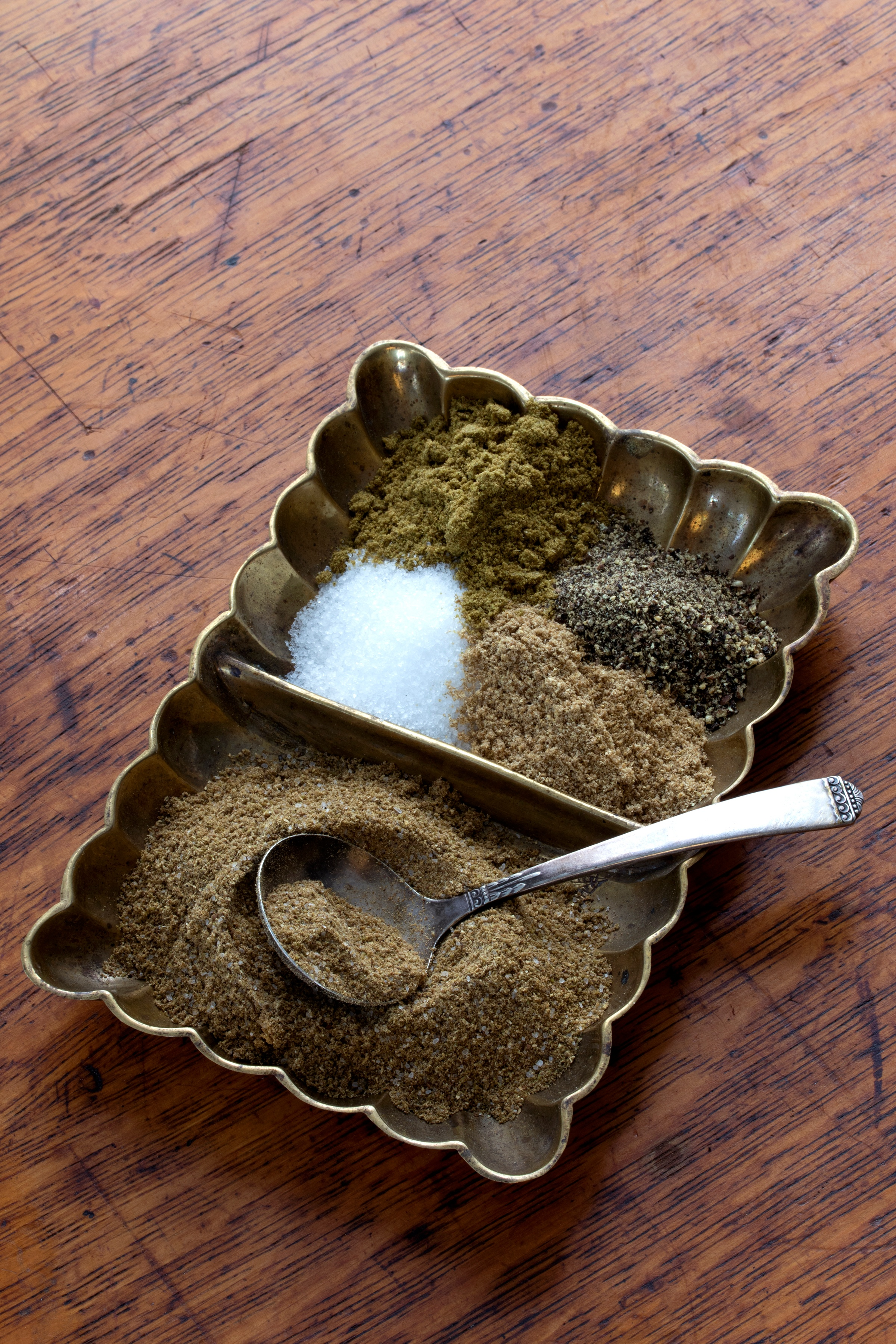 Punjabi Spice blend with cumin powder, coriander powder, black pepper, salt in a copper dish with a spoon on the table