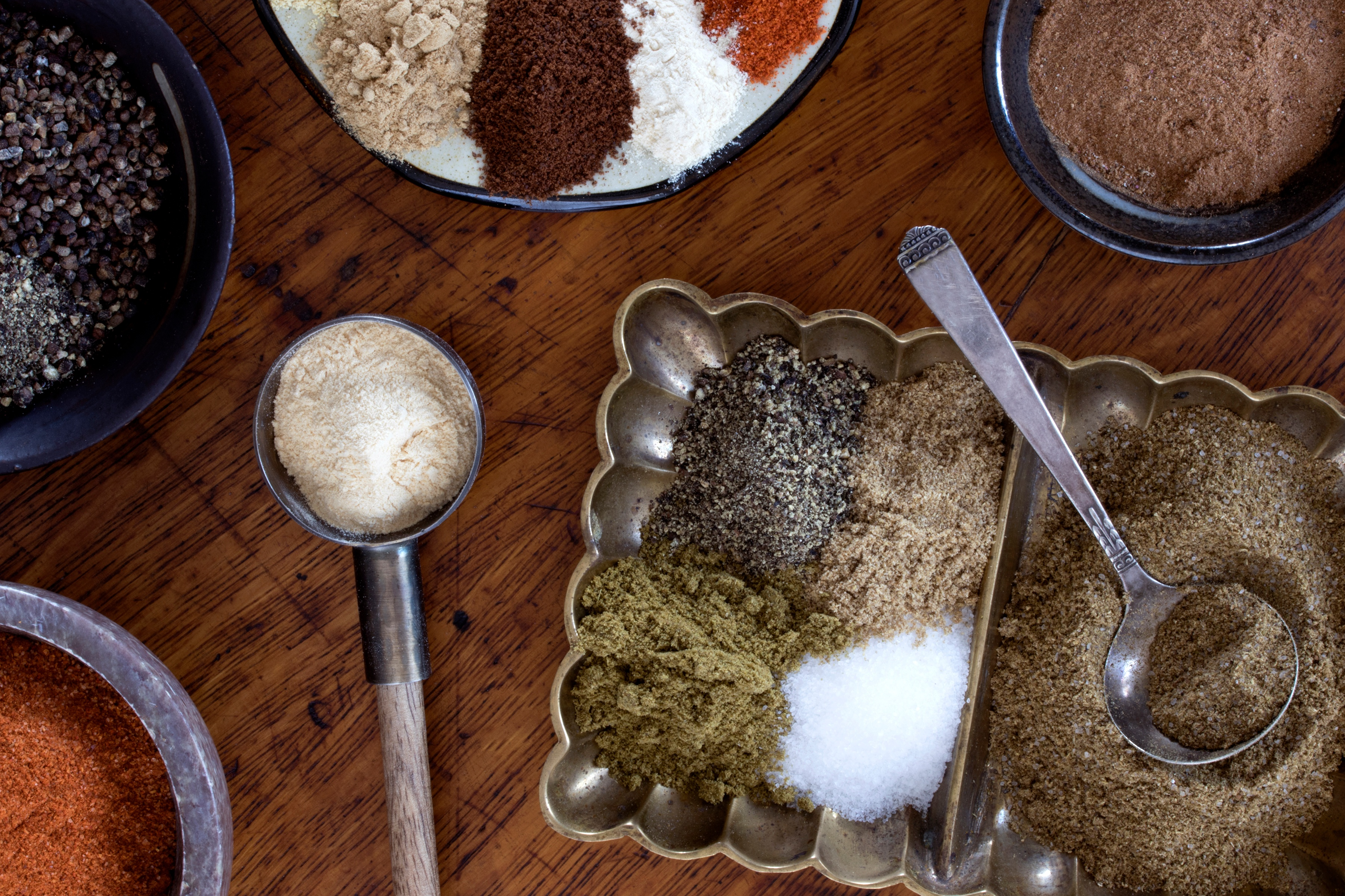 Lots of different spices, herb powders, and spice blends in bowls and containers with spoons on table