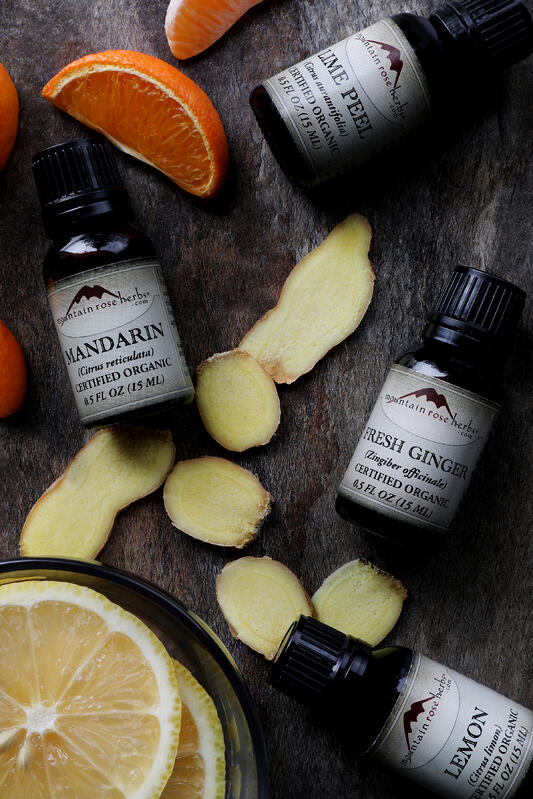 Slices of fresh ginger and fresh mandarins among bottles of essential oils