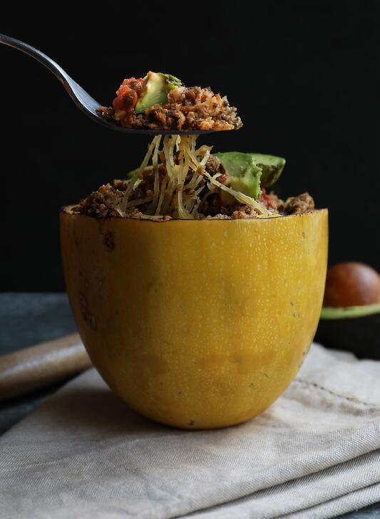 Fork lifting spaghetti squash noodles out of spaghetti squash bowl