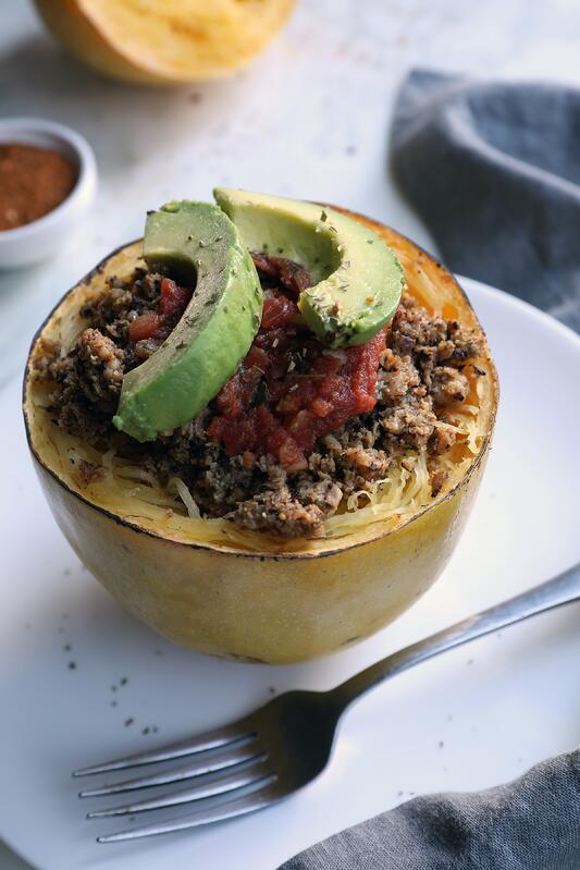 Half of spaghetti squash filled with mushrooms, herbs, avocado, salsa on plate with fork