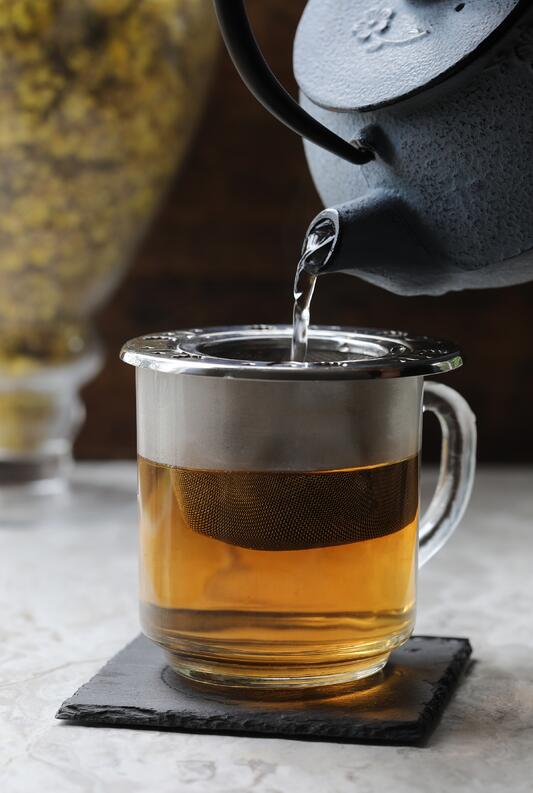 Cast iron tea pot pouring hot water into glass teacup with stainless steel tea infuser