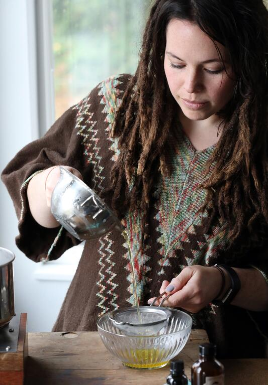 Woman pouring liquid out of double boiler and through sieve and into a bowl.