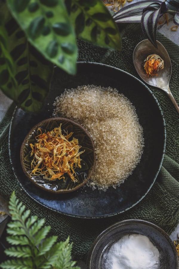 Small bowls with sugar, calendula flower petals, and baking soda.