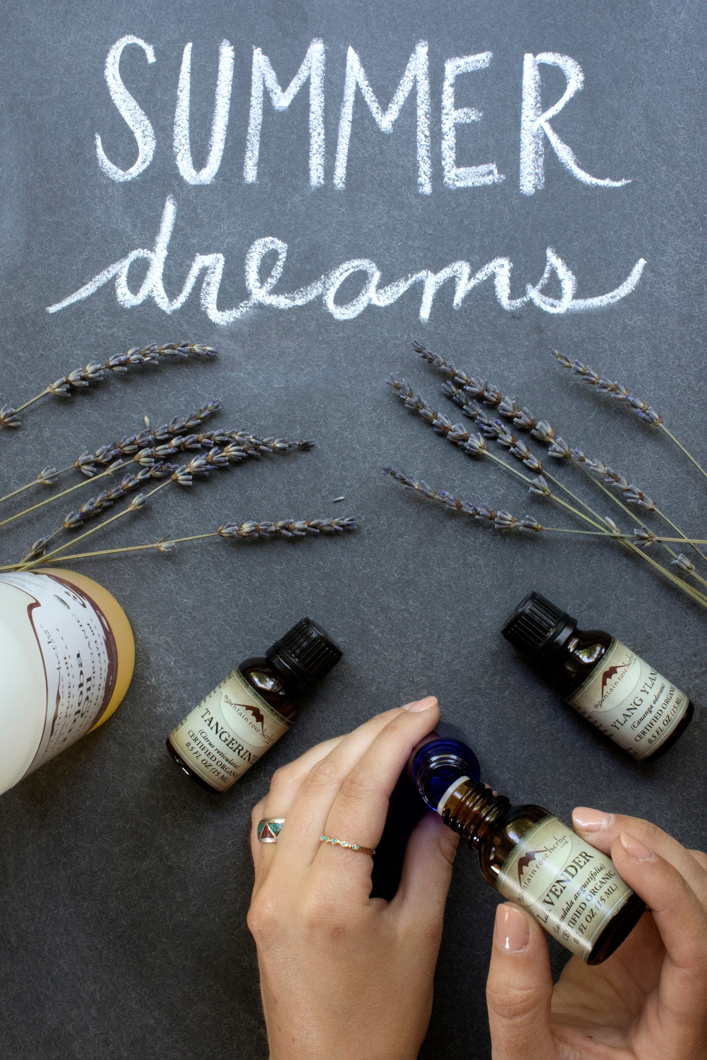 Hands putting drops of lavender essential oil into small glass bottle Summer Dreams essential oil fragrance recipe