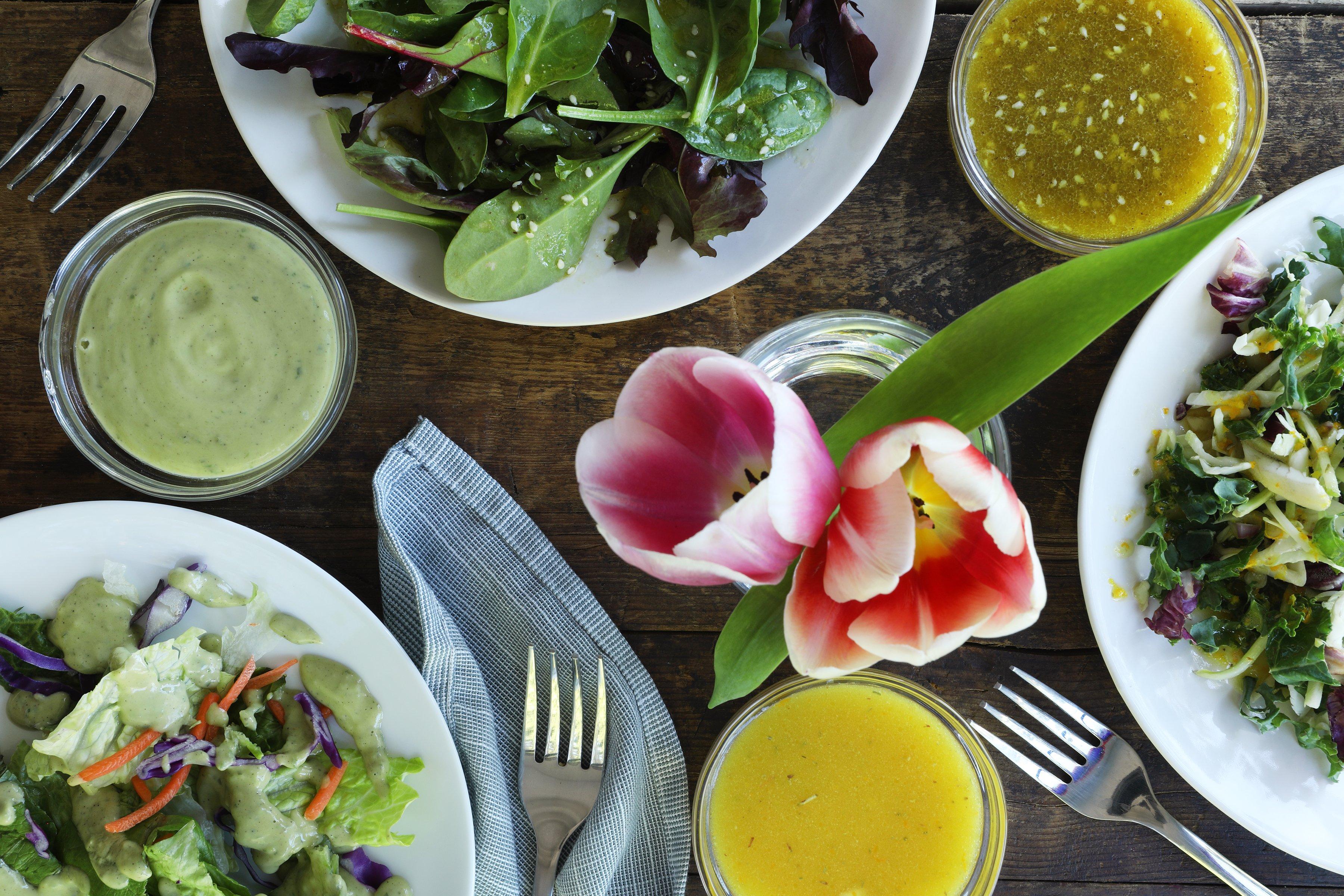 Three bowls of fresh salad greens arranged with fresh tulips and organic salad dressings.
