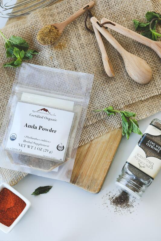 Bag of amla powder, smoked sea salt, mint leaves, and wooden spoons for making amla drink