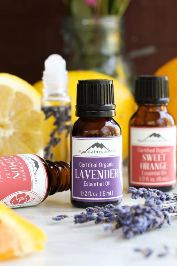 Bottles of lemon, sweet orange and lavender essential oils with fresh lavender and lemons slices.