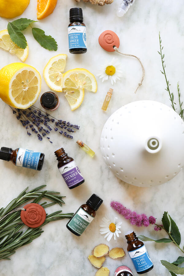 Two varieties of ceramic essential oil diffusers surrounded by essential oil bottles and fresh botanicals.