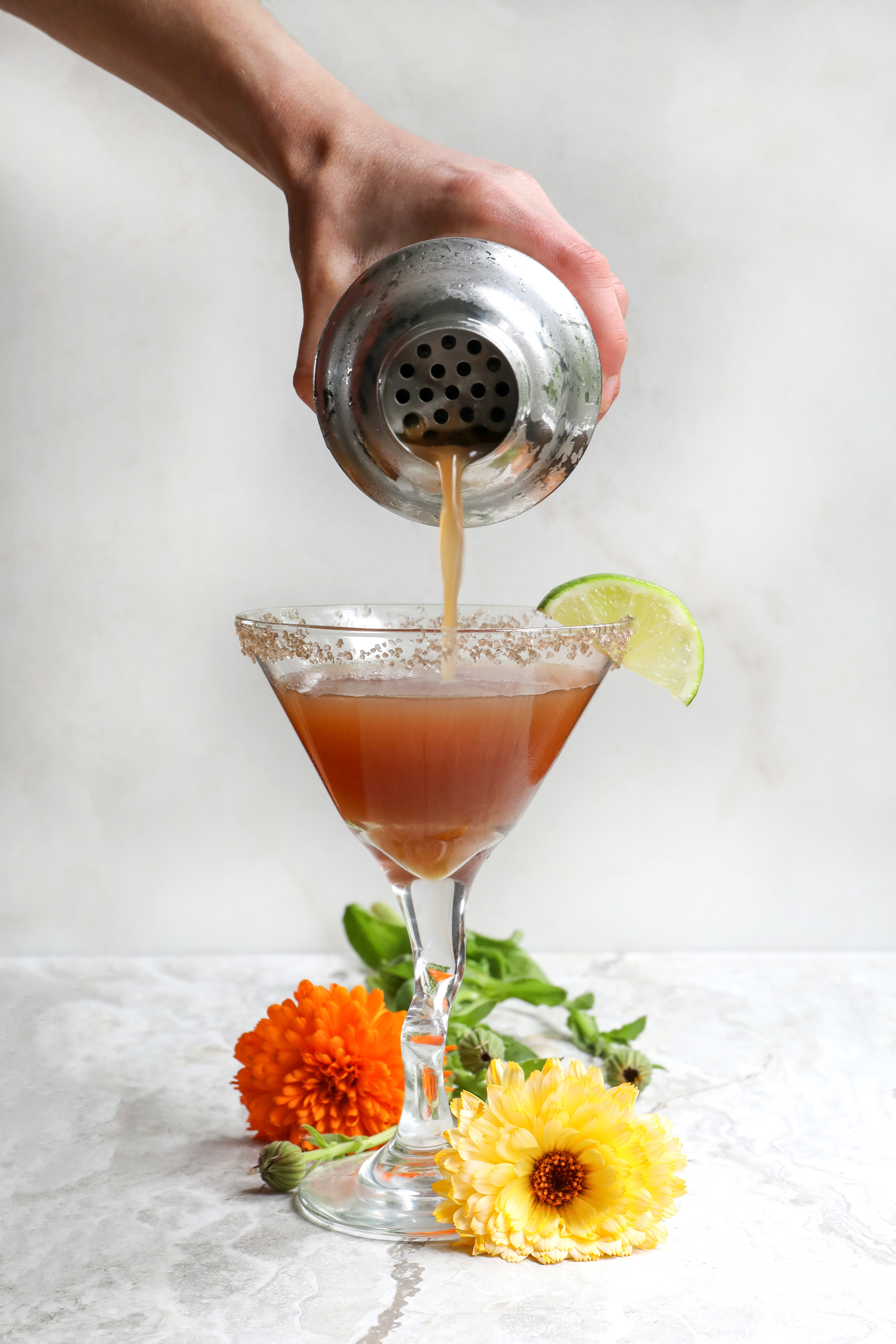 Hand pouring herbal cocktail into margarita glass with smoked salt on rim and flowers on counter