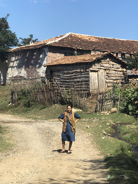 Susan Leopold of United Plant Savers poses in front of rustic log and brick farmstead in the Albanian countryside.