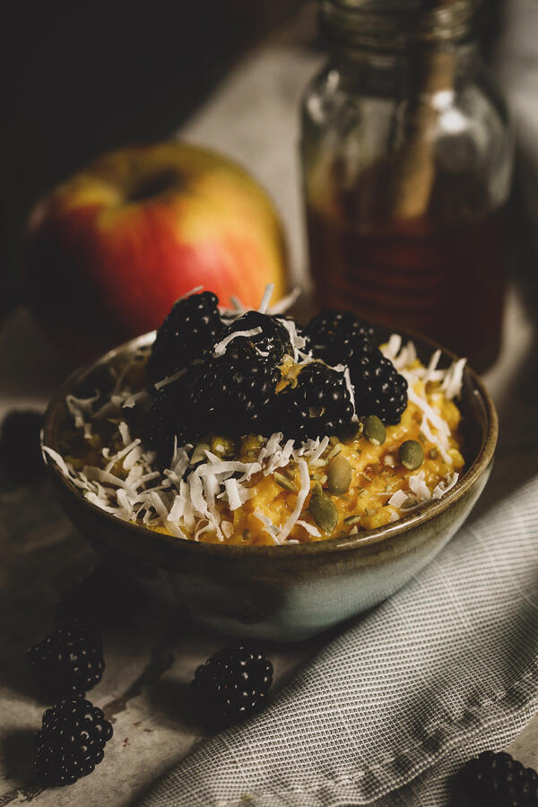 Bowl of golden congee with blackberries, coconut and pepitas.