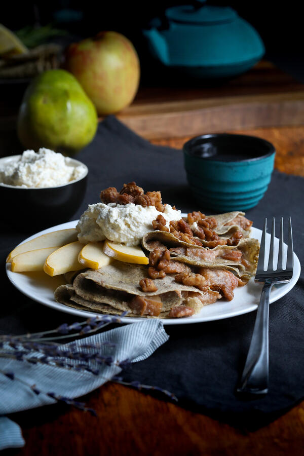 Gluten-free coconut buckwheat crepes with fried apples, sliced pears, spiced nuts and coconut cream.