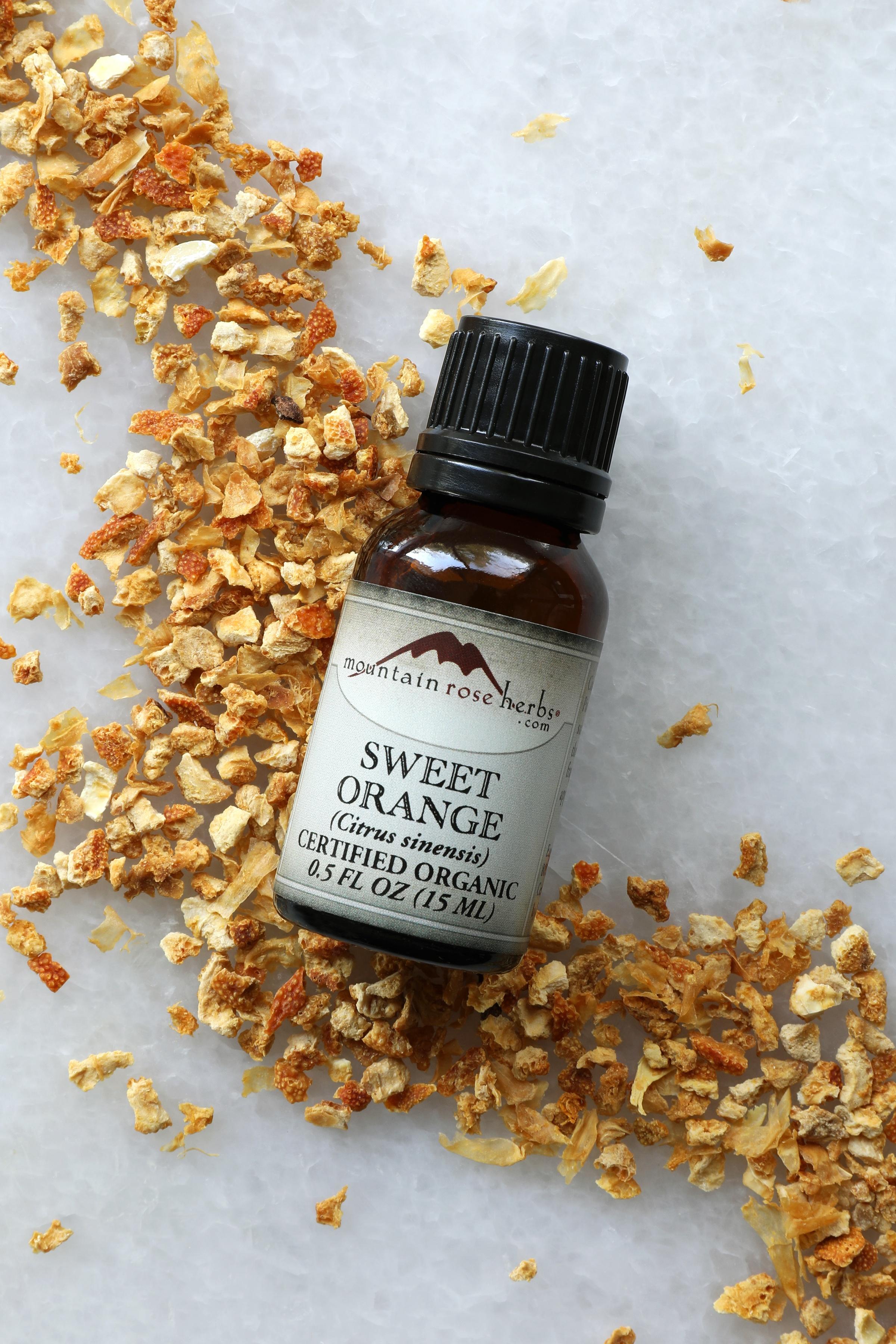 1/2 oz bottle of Mountain Rose Herbs sweet orange essential oil on dried orange peel