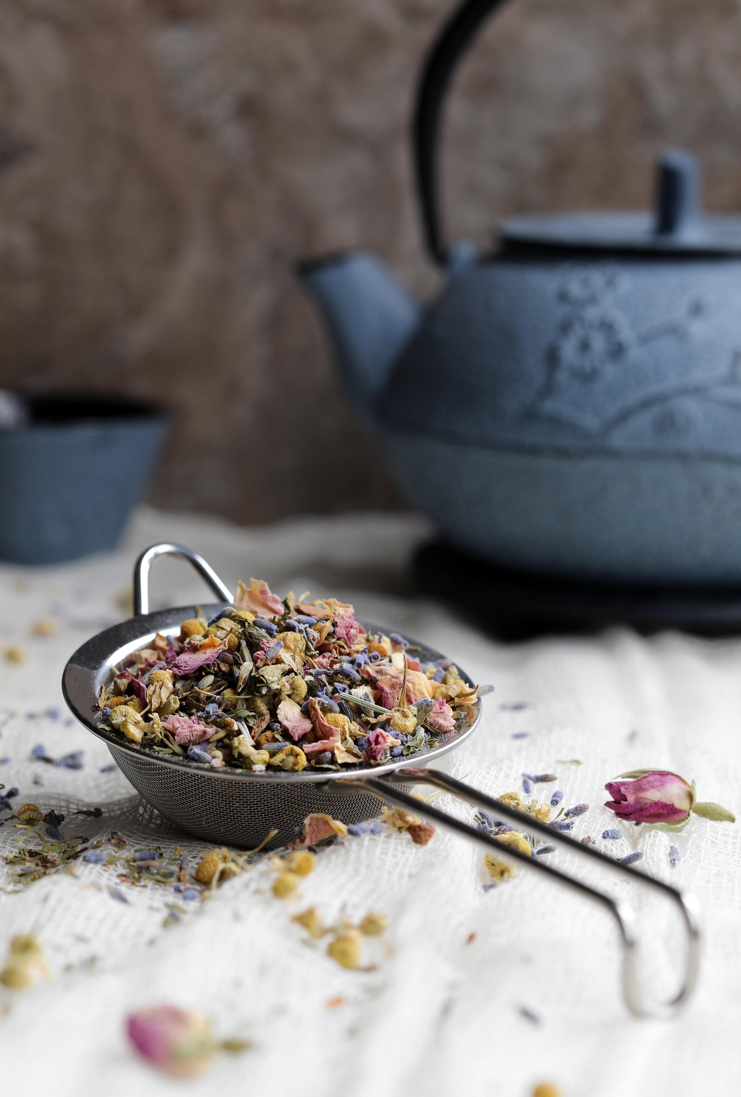 Metal mesh strainer holding floral herbal tea sitting next to cast iron tea pot
