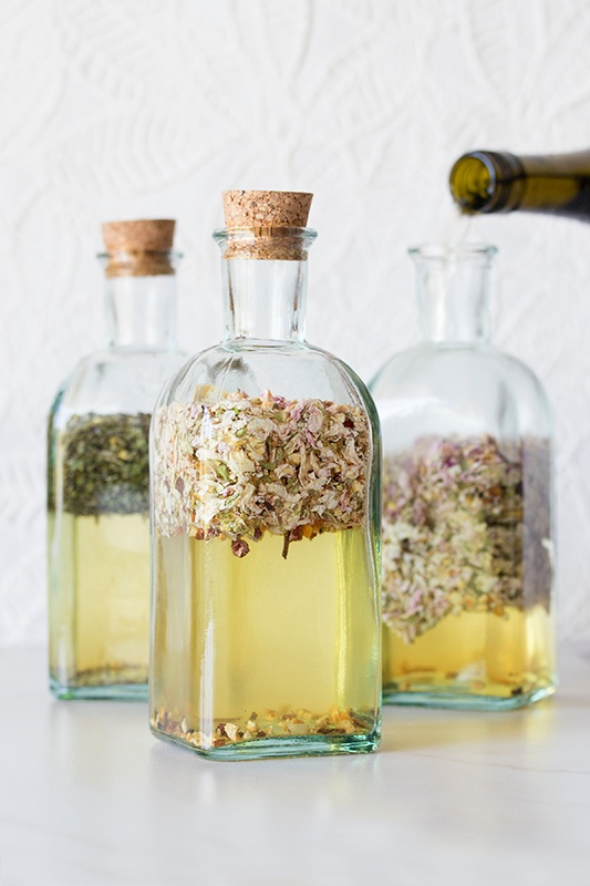 Three glass bottles with cork tops and herbs infused in wine