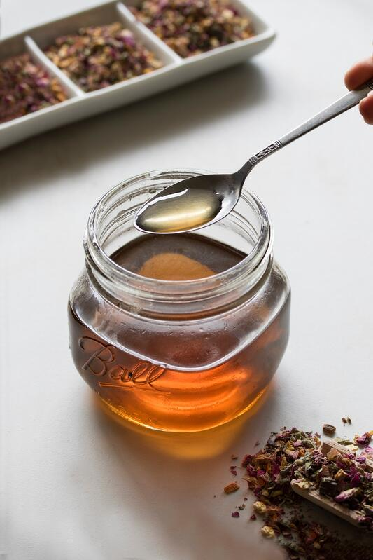 Herbal syrup in a glass mason jar with a spoon and loose leaf tea