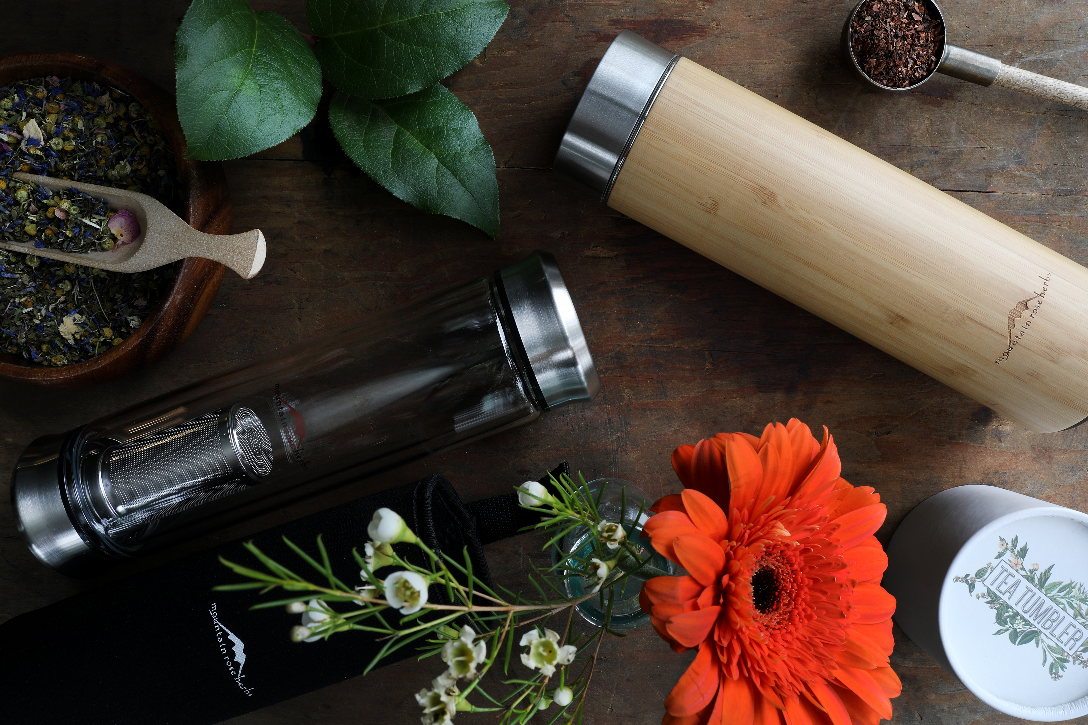 Wooden and glass hot beverage containers sirrounded by colorful flowers, plants and herbal teas.