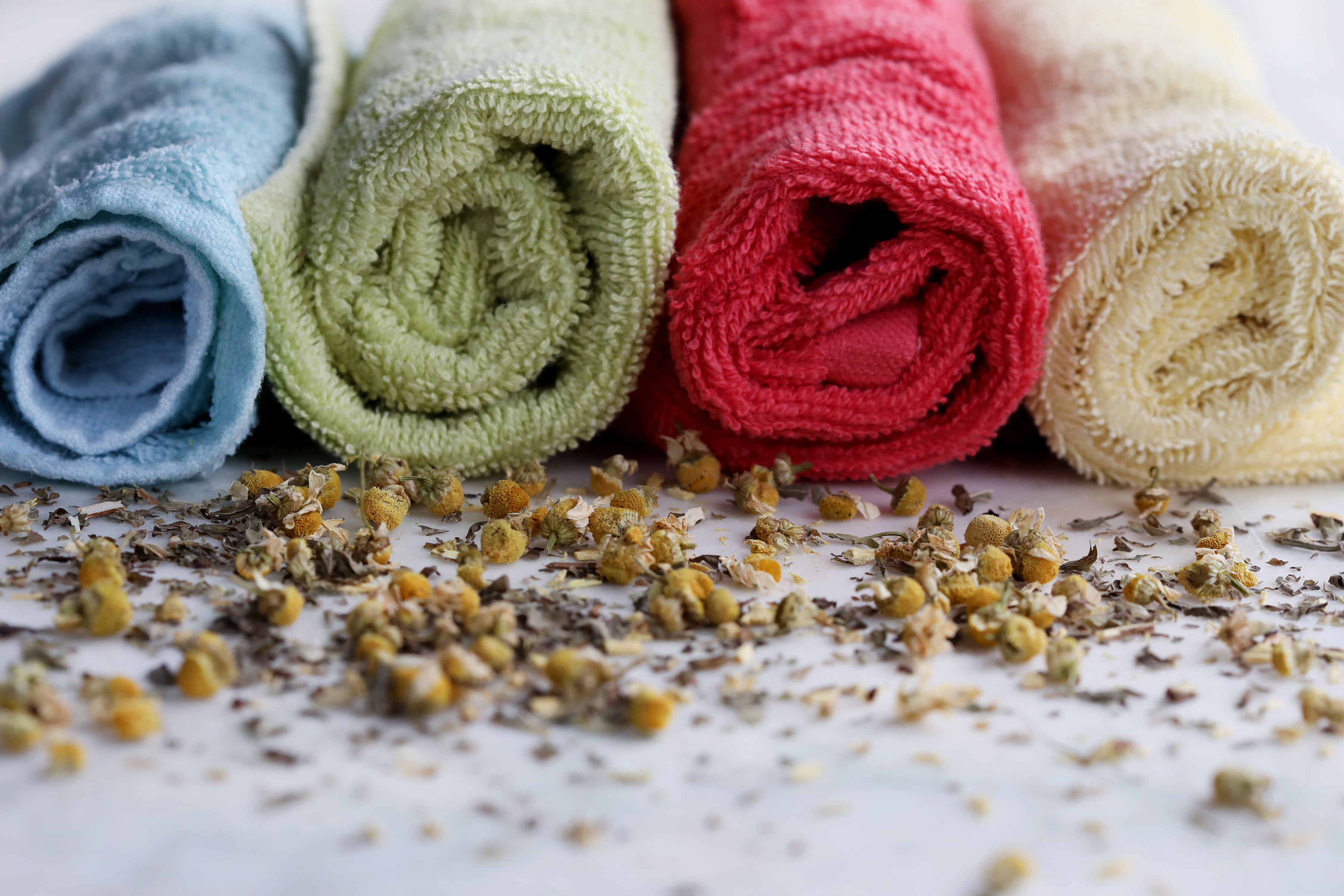 Colorful rolled towels with sprinkled chamomile on table in front of them.