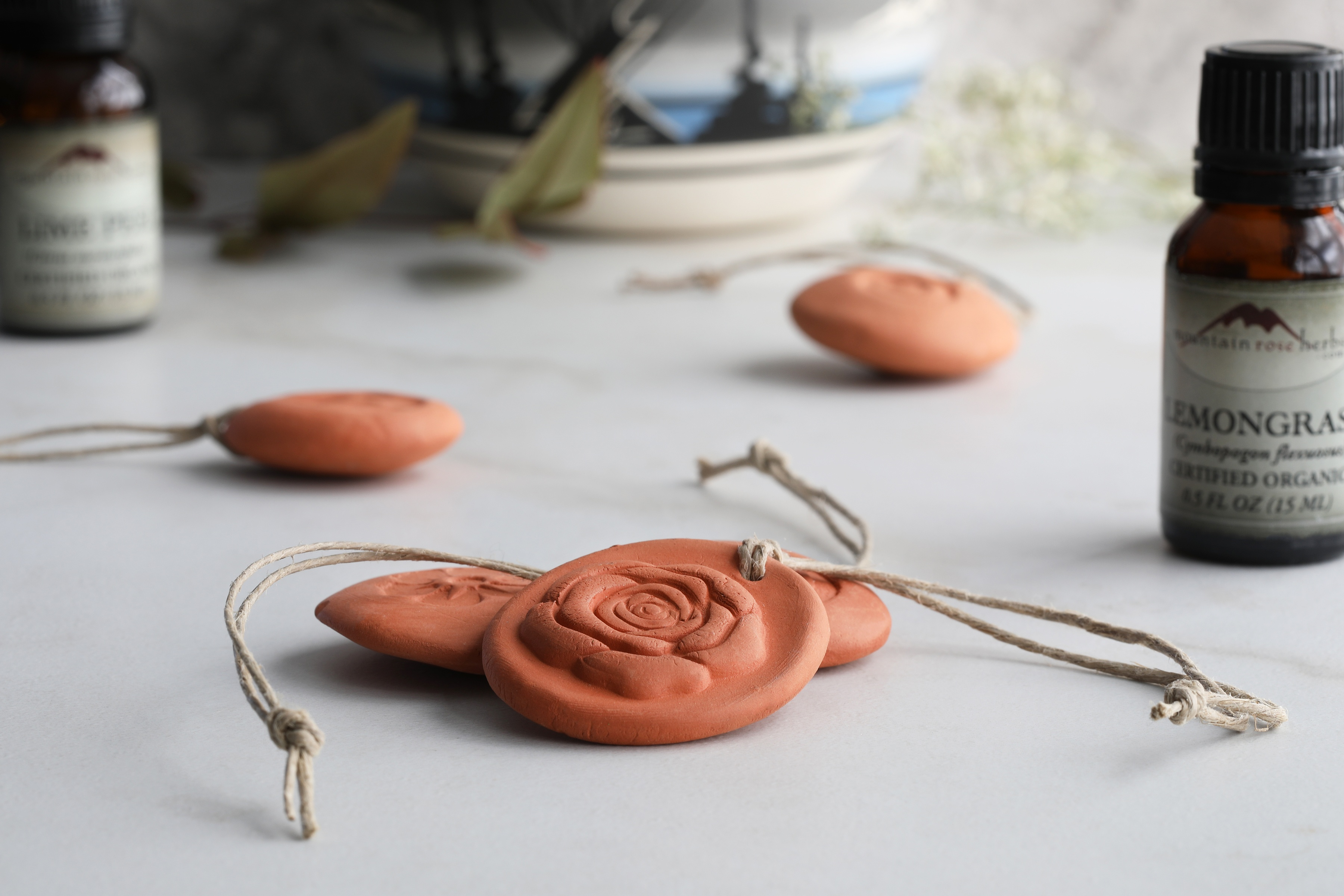 Small terra cotta hanging diffusers laying on surface with lemongrass essential oil