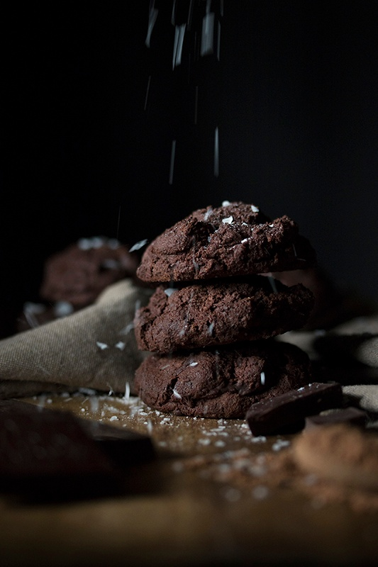 Stack of four chocolate cookies with salt sprinkles on black background