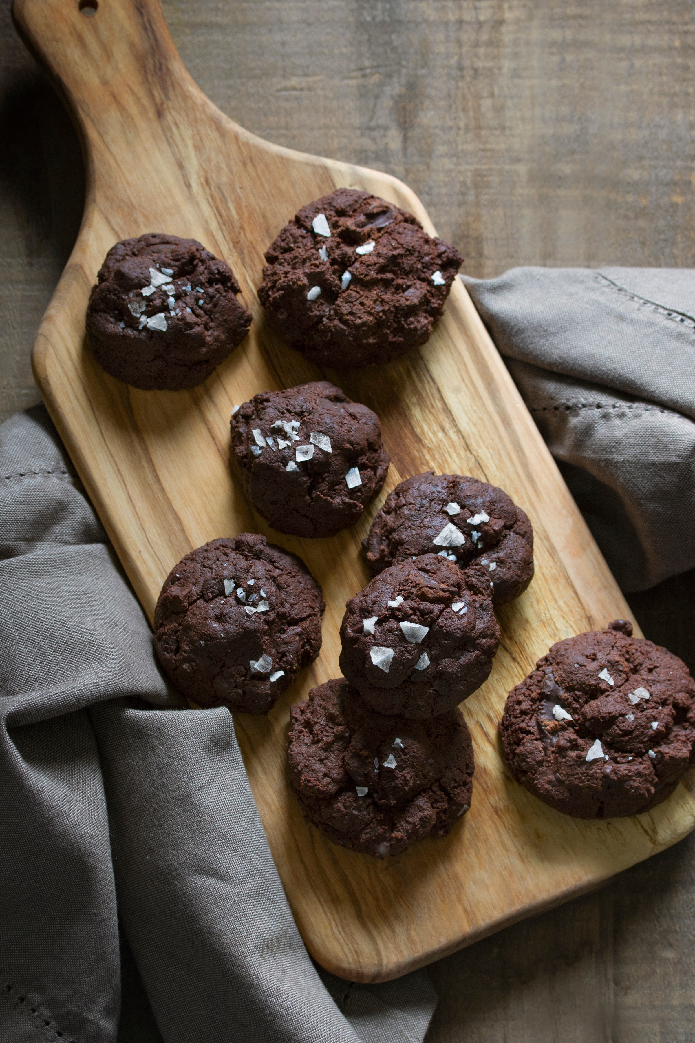 Chocolate chip cookies with flake salt on cutting board with cloth napkin on table
