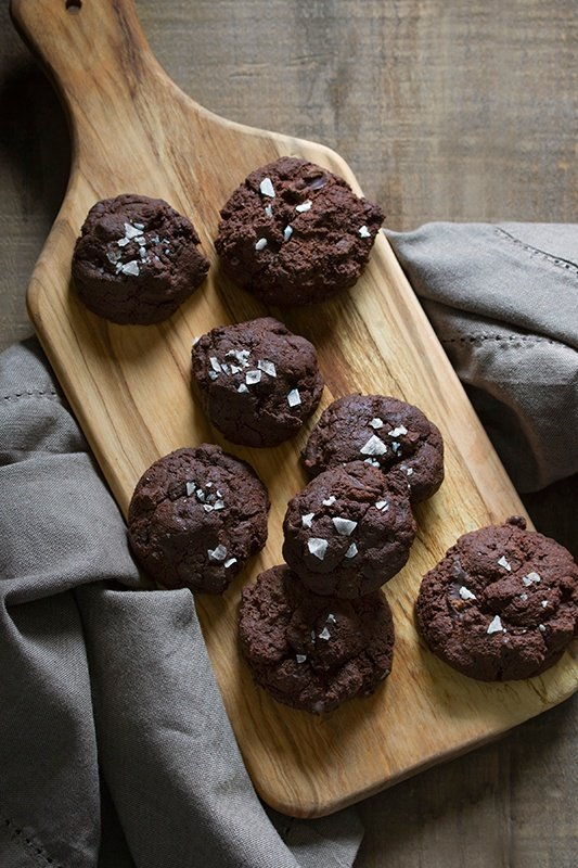 chocolate cookies on a cutting board with sprinkles of salt