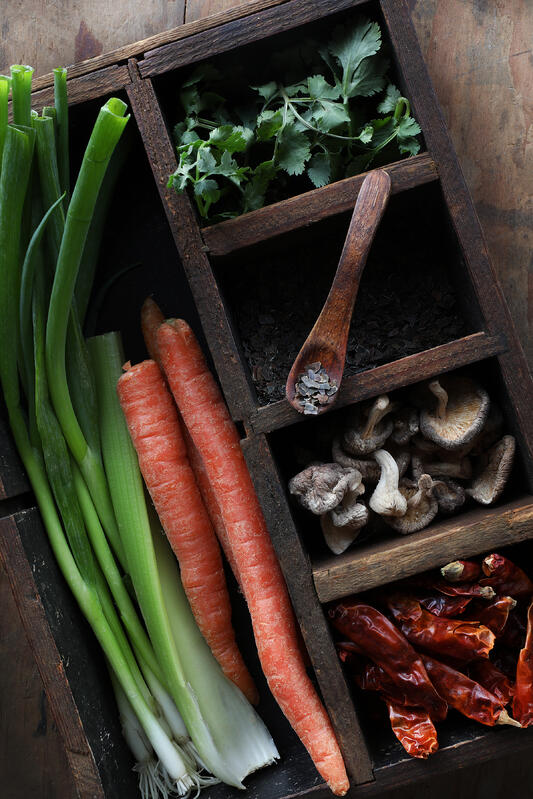 Fresh and dried colorful tom kha soup ingredients in a rustic wooden tray.