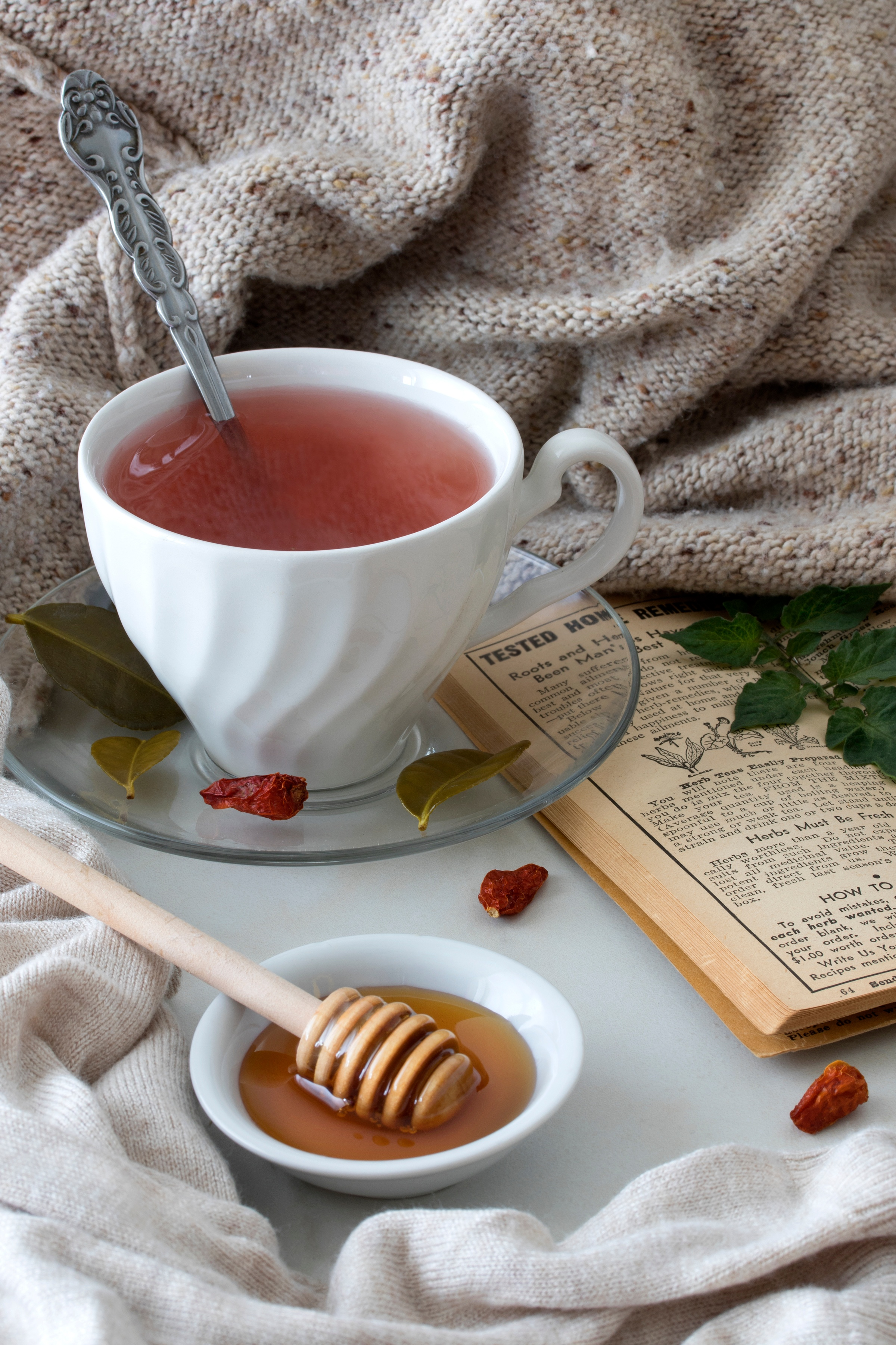 ceramic mug filled with tom kha fire cider next to blanket and honey