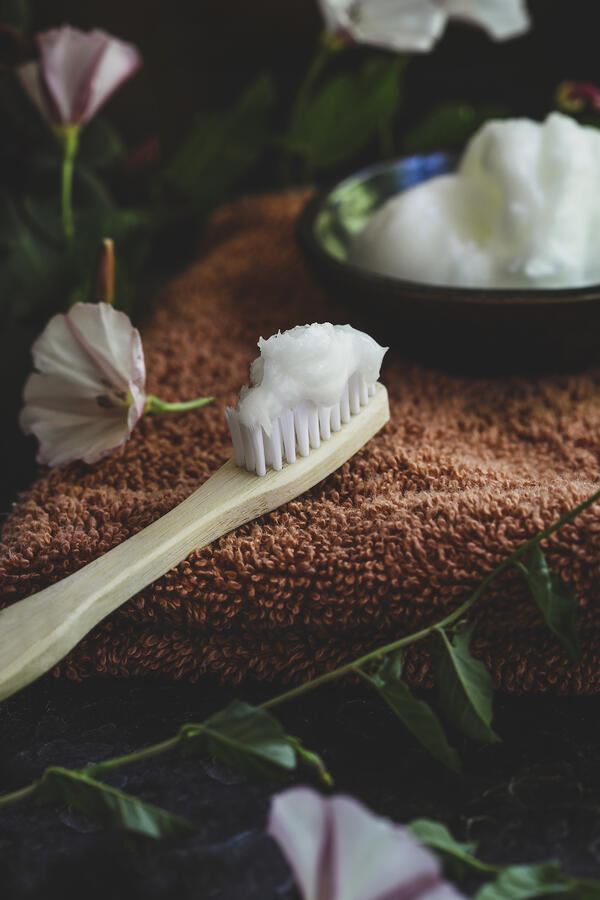 A bamboo toothbrush with a dollop of homemade toothpaste on it.