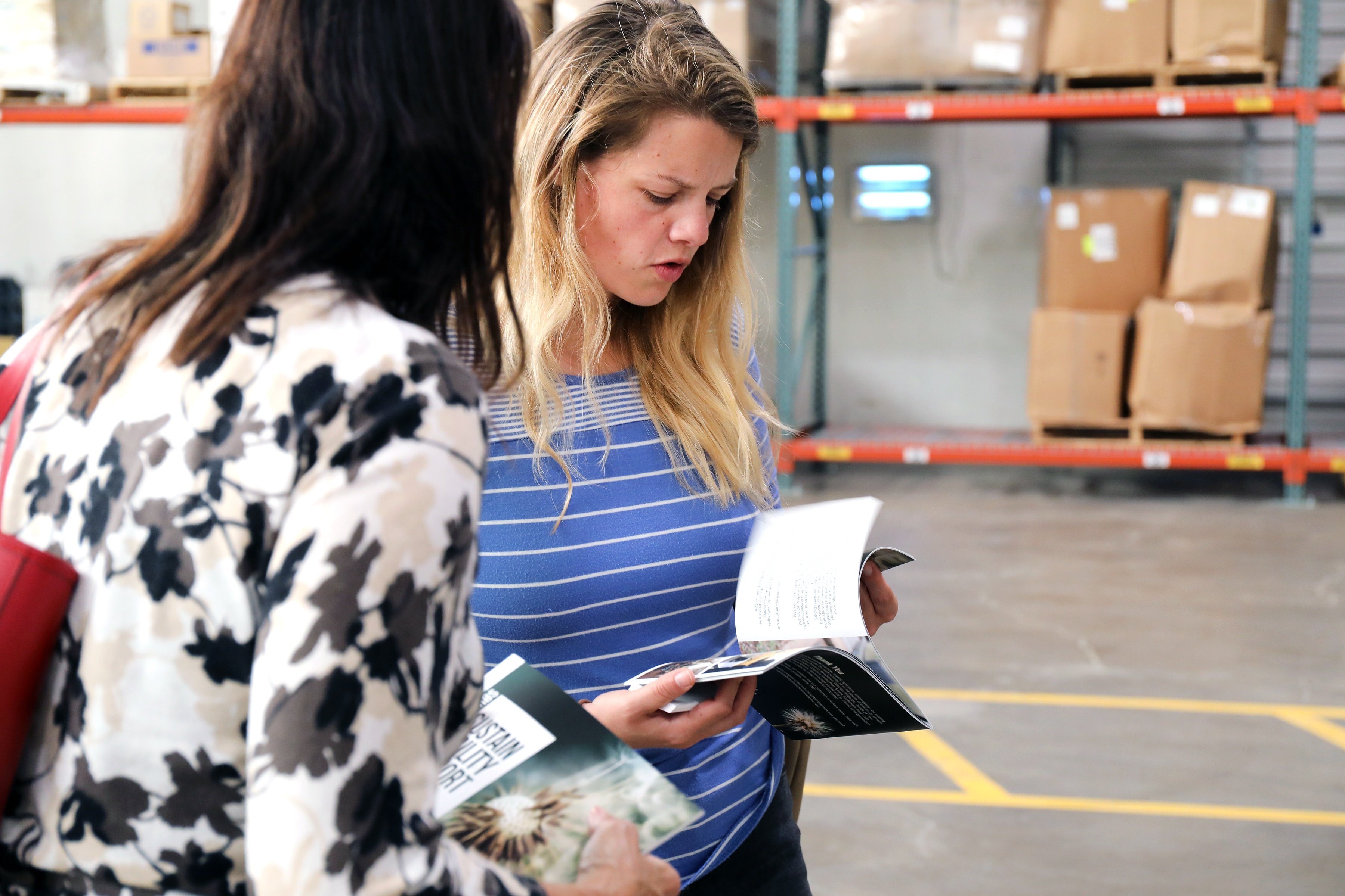 Two women reviewing pamphlet in warehouse setting