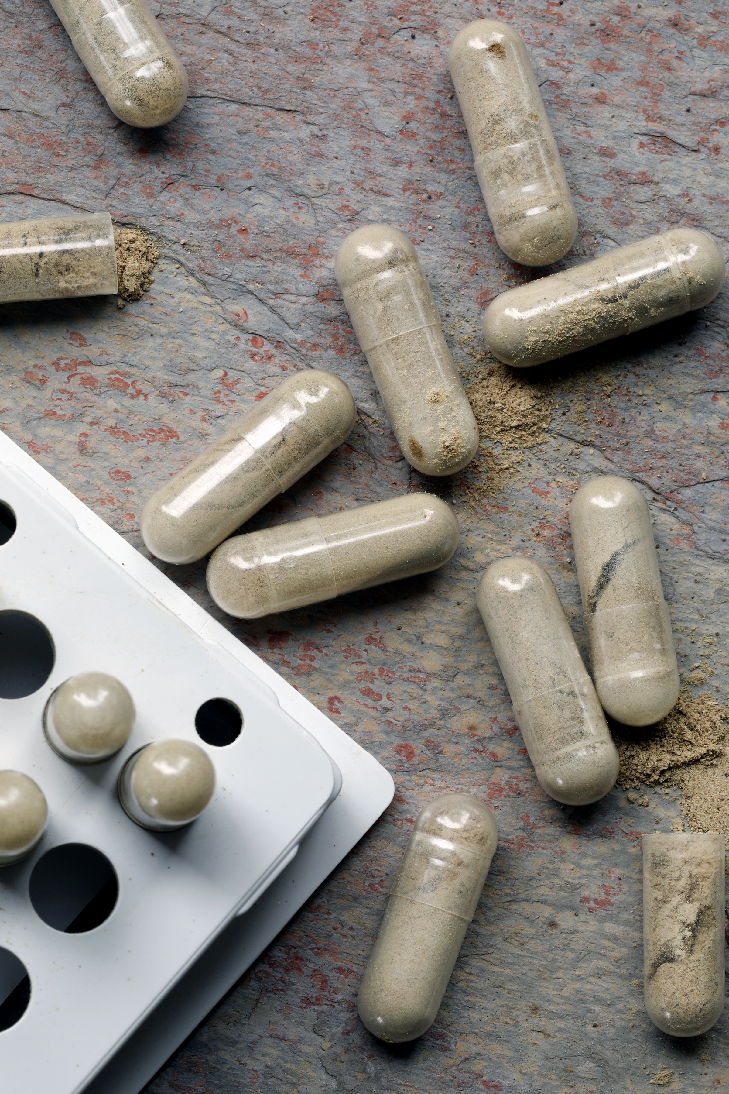 Capsules filled with triphala powder laying out on granite counter