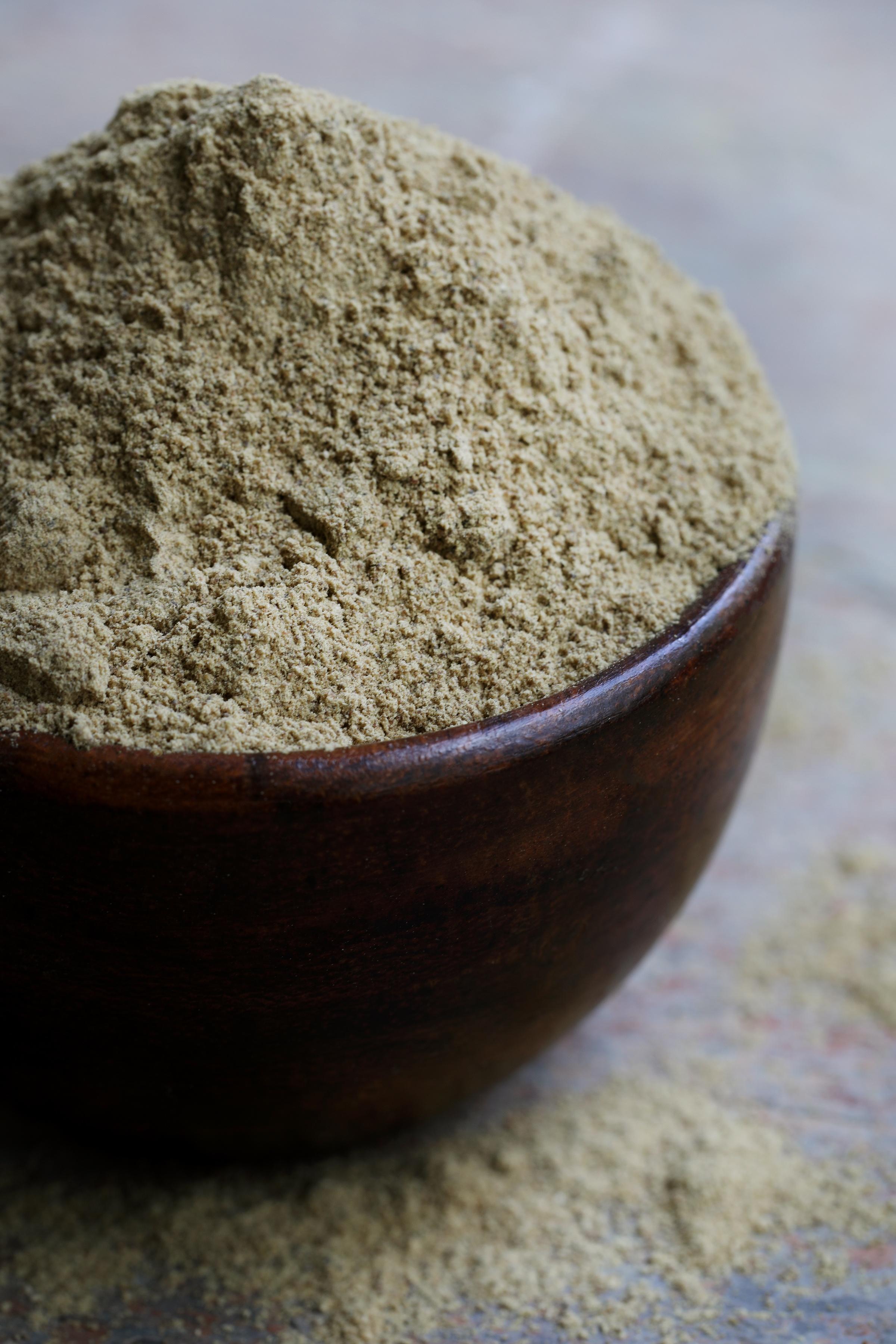 Wooden bowl full of organic triphala powder