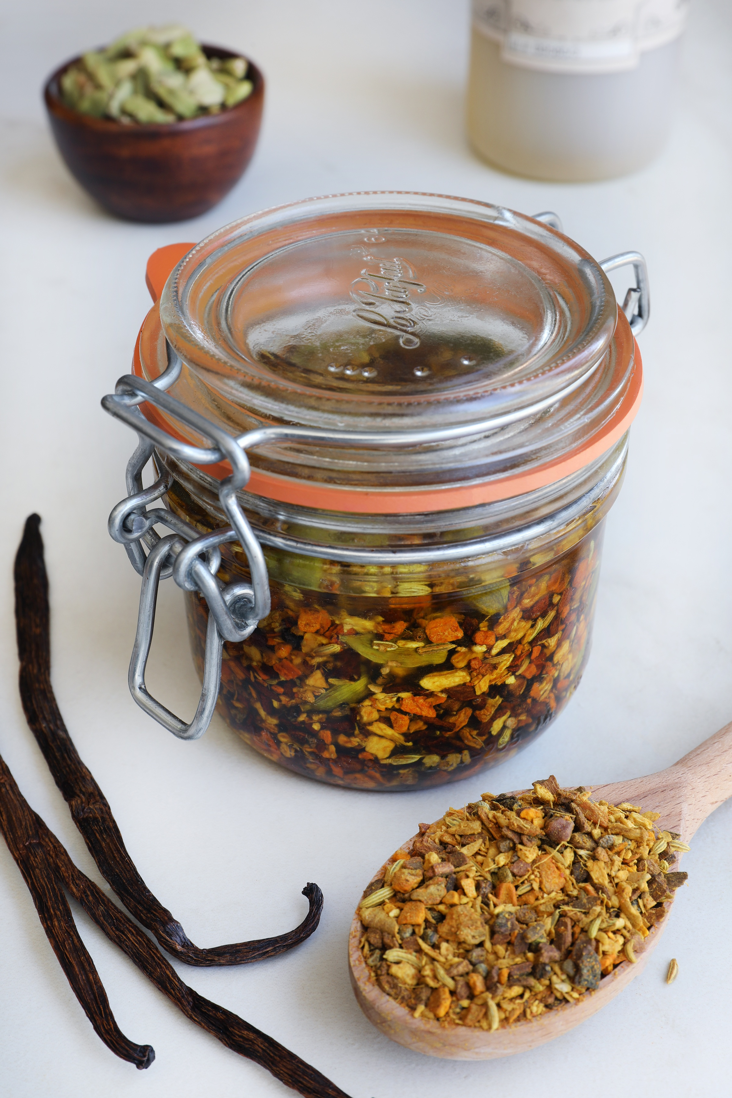 Glass pantry jar with turmeric chai tea blend infused in oil with vanilla beans