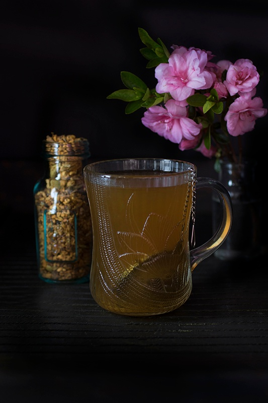 Single glass mug of turmeric chai tea sitting next to bouquet of flowers