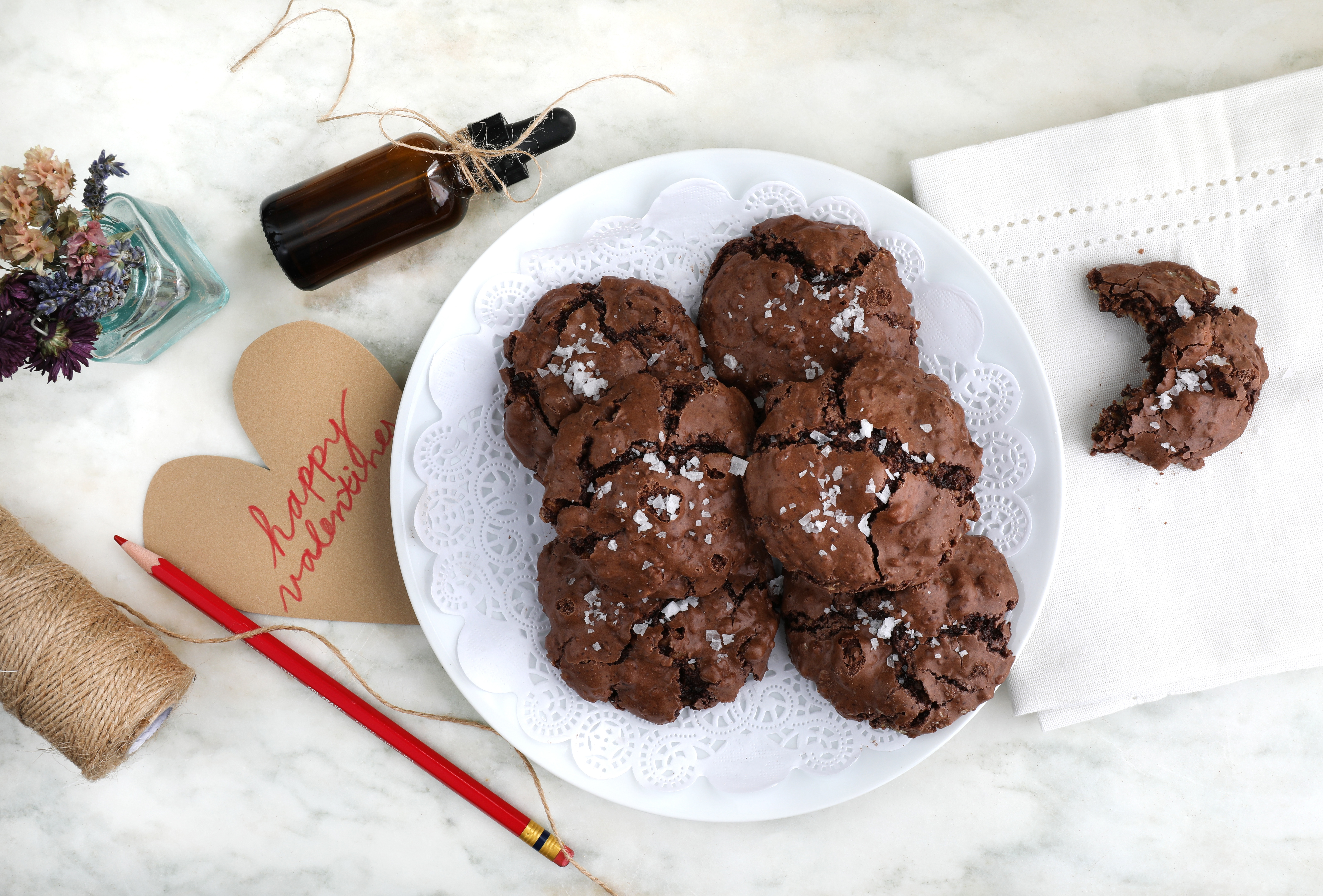 Chocolate chip cookies on plate on counter with flowers and handmade card and string