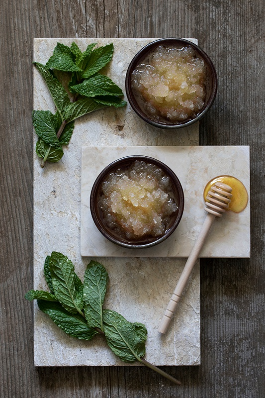 bowls of sugar scrub with mint leaves and honey