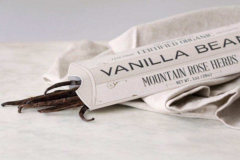 Rectangular paper package holding a bundle of vanilla beans lying on counter with fabric