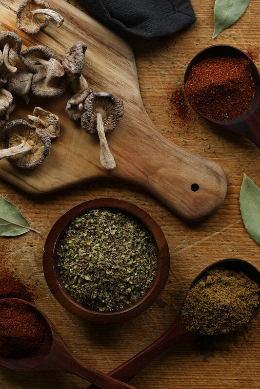 Spices, chili pepper powders, and dried organic shiitake mushrooms are assembled together before being added to the crock pot for a hearty vegan chili. Bay leaves, ancho pepper powder, and cumin seed powder add a depth of flavor and spice.