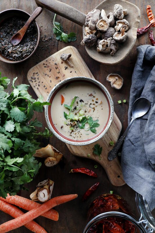 Cup of creamy tom kha thai coconut soup surrounded by fresh ingredients and herbs.