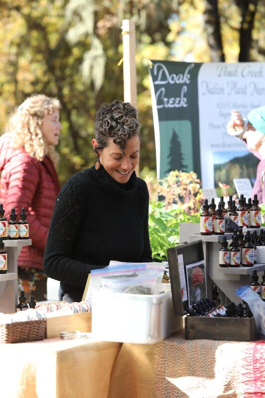 A vendor at a booth with many herbal products in an outdoor setting.