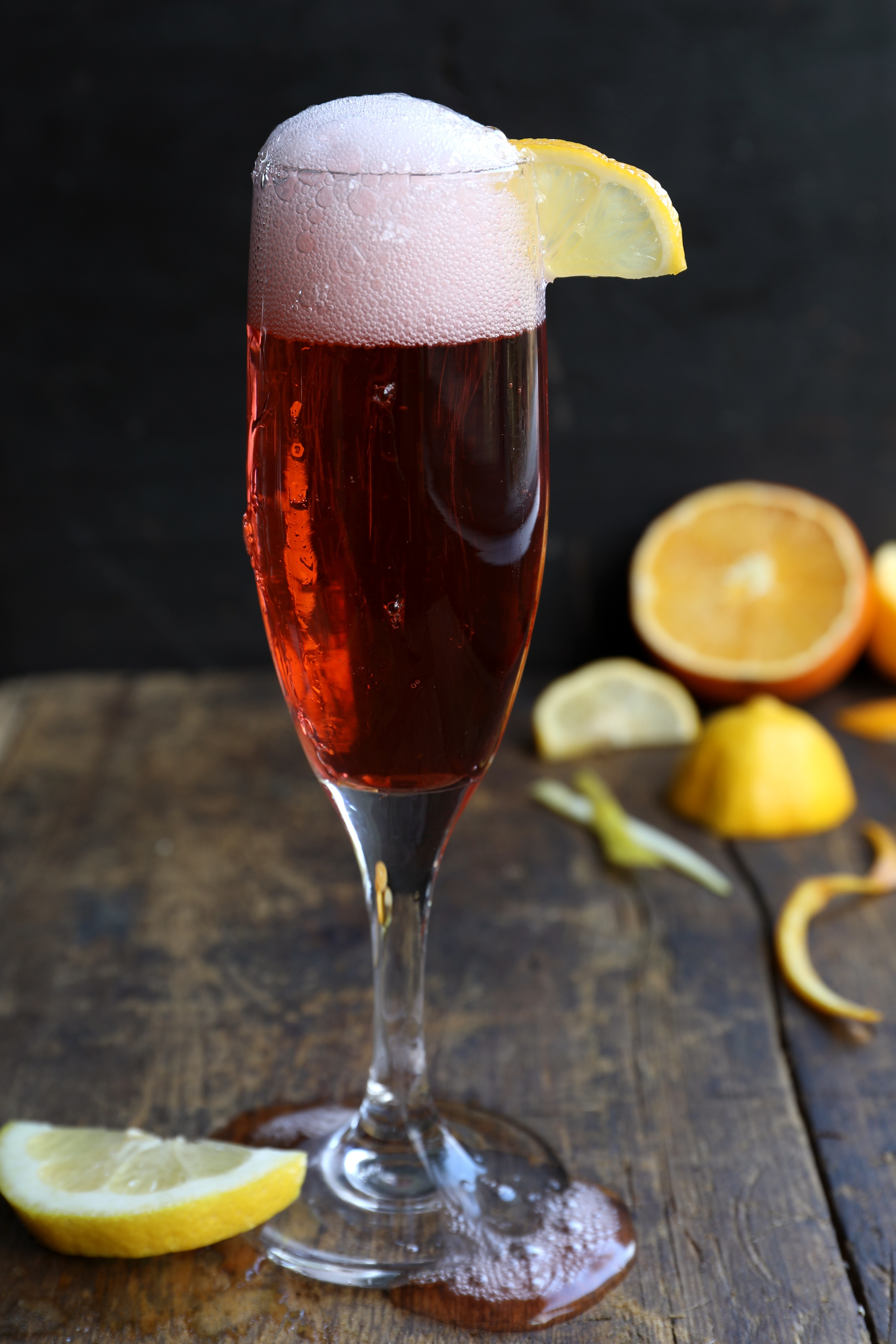 Red champagne drink with bubbly top, made with campari, vermouth, and organic gin