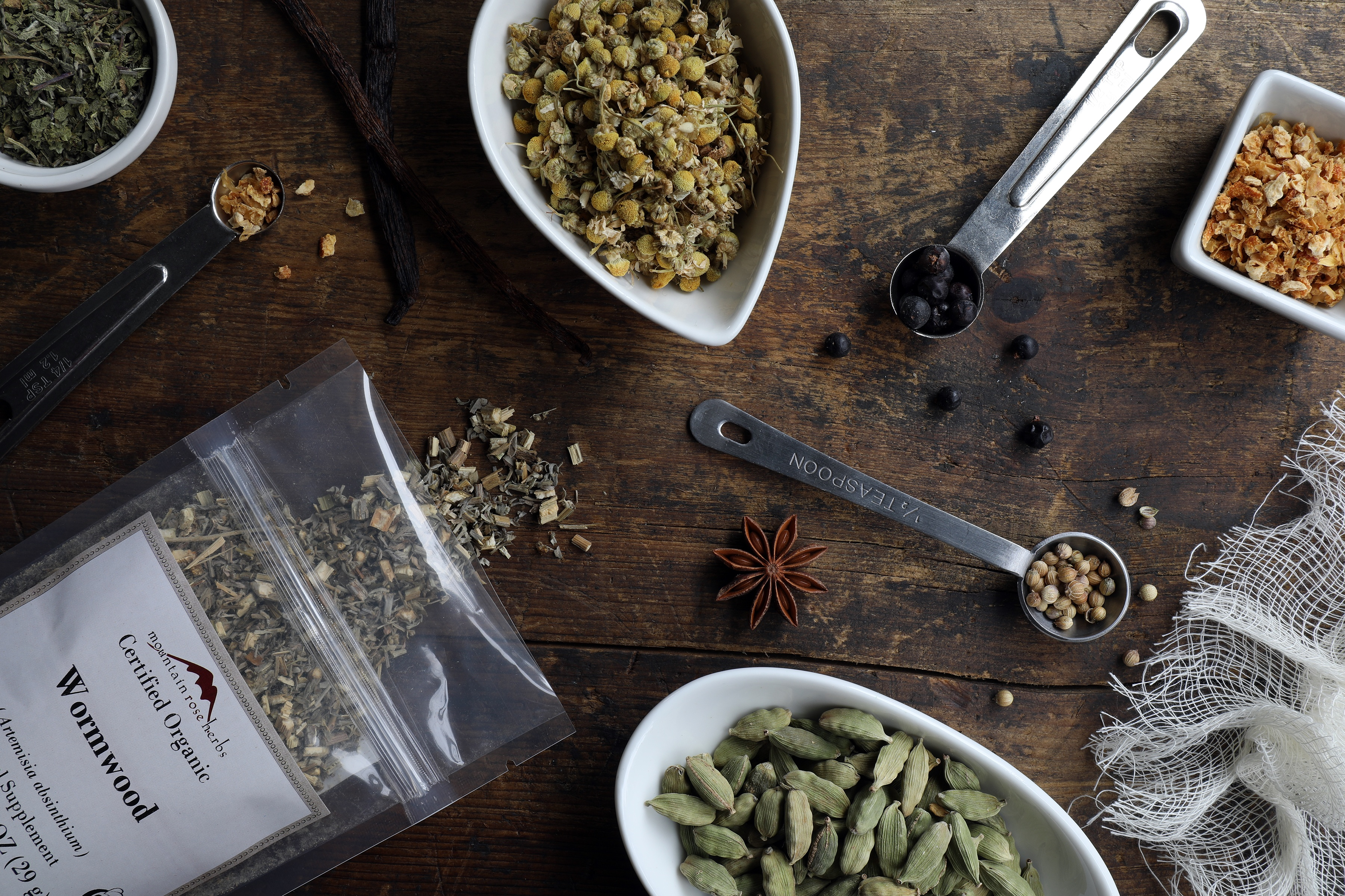 Ingredients for making homemade vermouth laying in bowls on counter including cardamom and wormwood and orange peel
