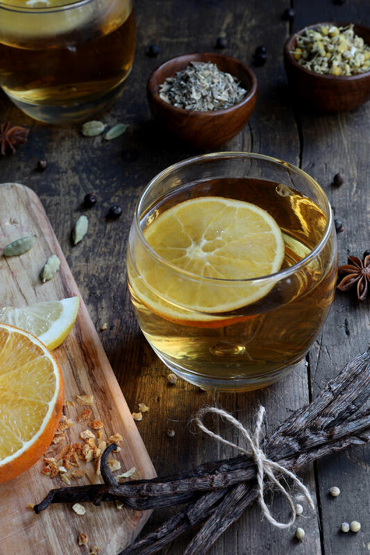 Glass cup filled with golden liquor, with an orange slice and various loose botanicals surrounding it, on a rustic table.