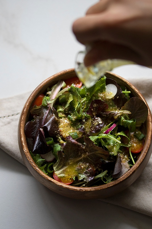 Vinaigrette pouring onto green salad