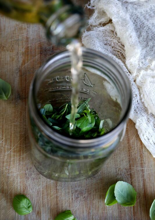 Pouring vingar into mason jar with fresh herbs.