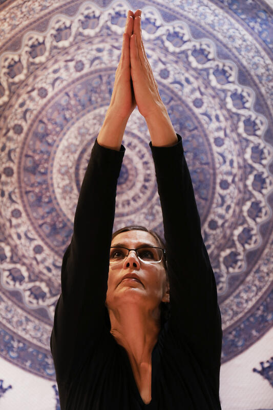 Woman practicing yoga in front of a tapestry