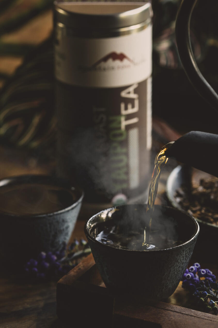 Hot yaupon tea being poured into a cup with steam rising.