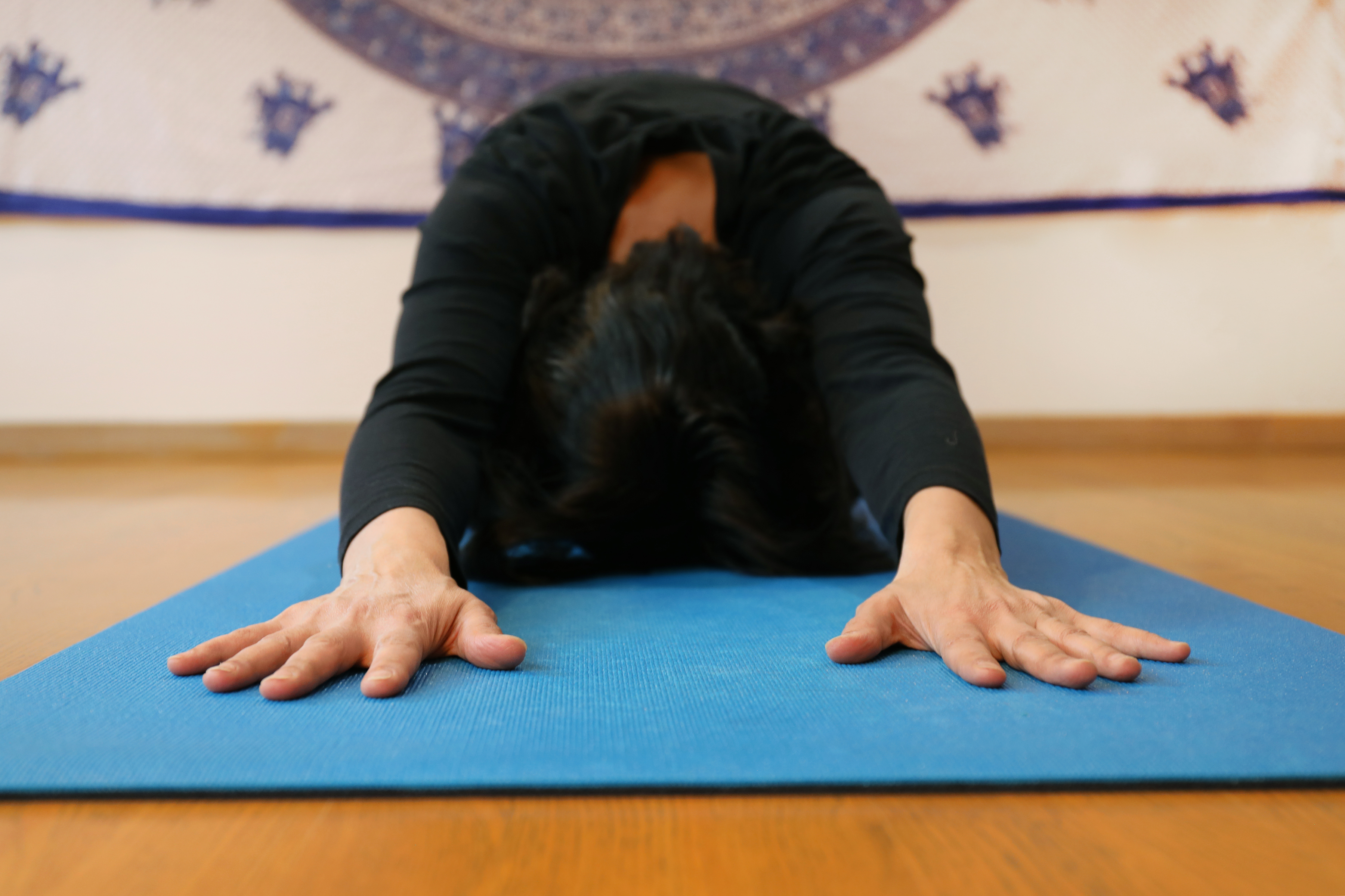 Woman practicing yoga with a tapestry in background.