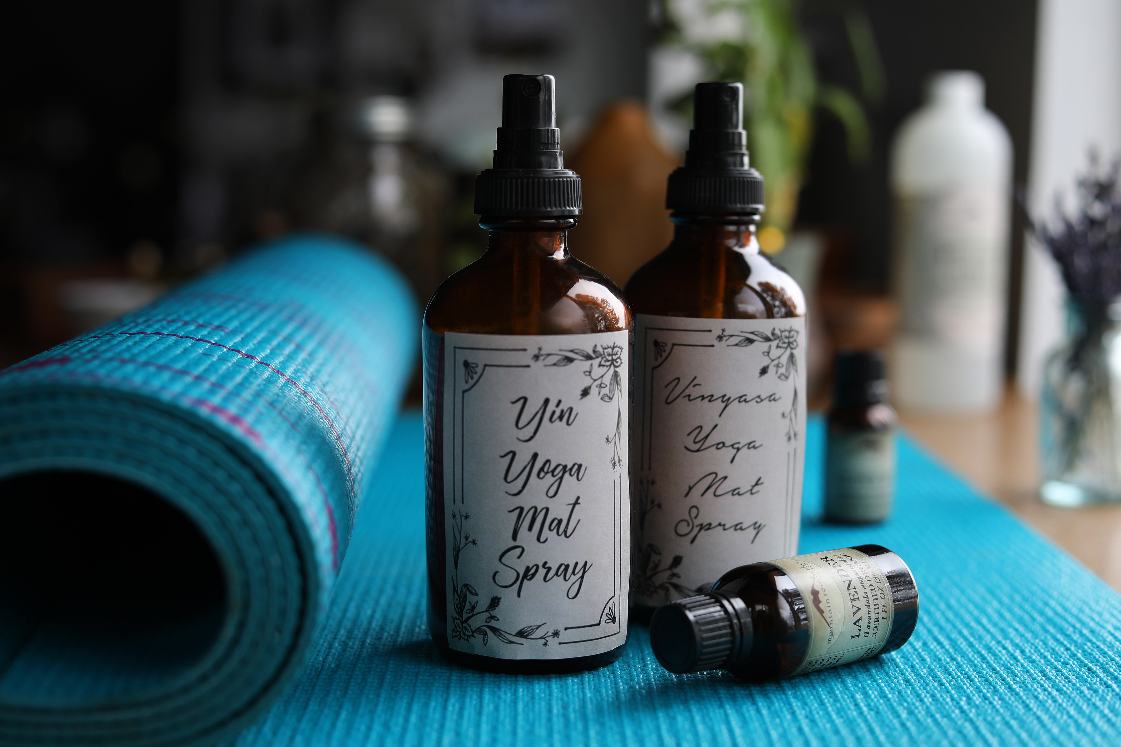 Partially Rolled up yoga with two bottles of homemade spray and bottles of essential oils around.